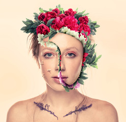Portrait of young woman with flowers on face against white background
