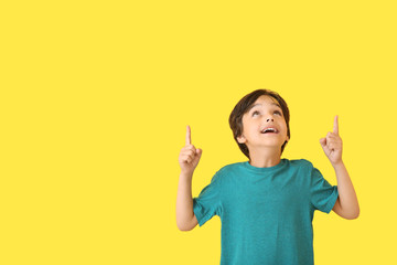 Happy little boy pointing at something on color background