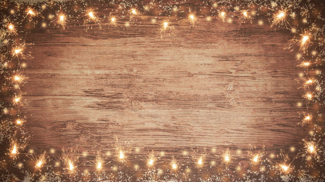 frame of lights bokeh flares and sparkler isolated on rustic brown wooden texture - holiday New Year's Eve background banner