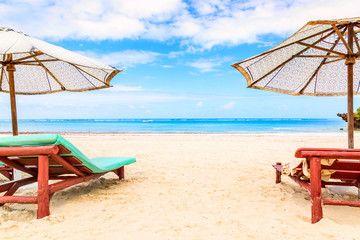 Printed kitchen splashbacks Zanzibar Sun loungers under umbrellas on the sandy beach by the ocean and cloudy sky. Vacation background. Idyllic beach landscape.