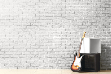 Modern bass guitar near white brick wall