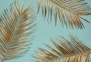 Wall Murals Palm tree Gold painted date palm leaves on desaturated turquoise background