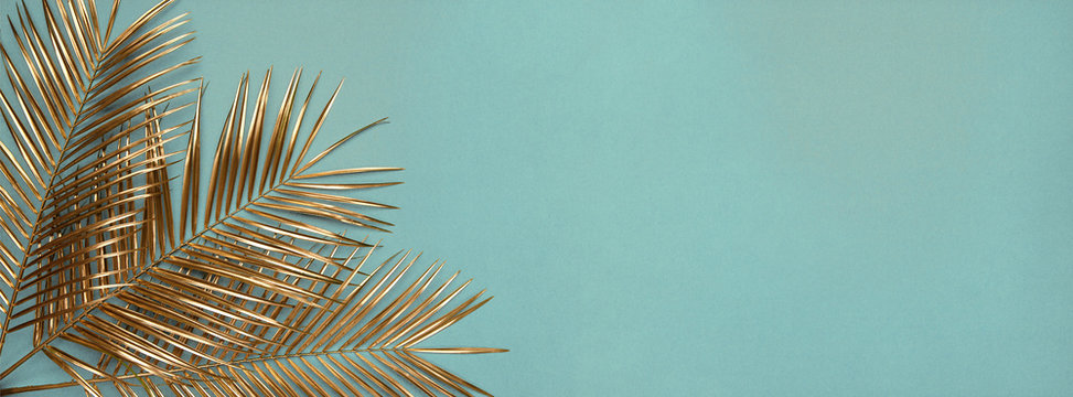 Three gold painted date palm leaves on desaturated turquoise background