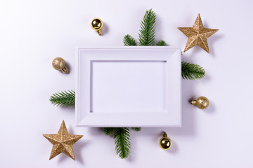 Christmas composition. White photo frame, fir branches, gold decoratios on white background. Copy space.