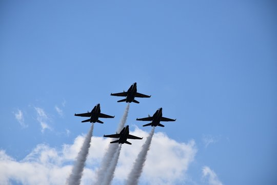 Low angle shot of four fighter jets with big trails maneuvring in the sky during an air show