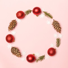Red Christmas shiny balls and fir twigs on pale pink background. Christmas ornaments arrangement...