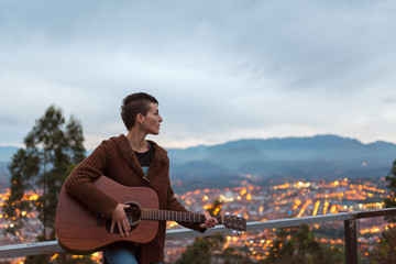 Horizontal stock photography. A young, attractive girl with short hair plays the guitar in the street, just outside the city at dusk. You can see the city lights on in the background.