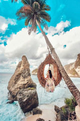 Tuinposter Bali Beautiful girl on swing coconut palms on beach at Daimond beach, Nusa Penida island Bali ,Indonesia