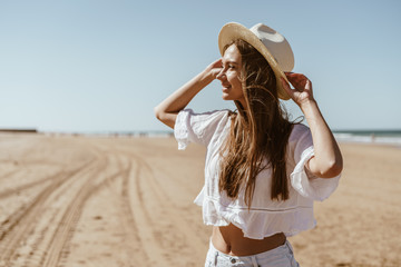 attractive european woman stands on the beach and looks into the distance, holding her hat with her hands