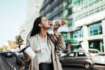 girl eagerly eats a hamburger on the go against the background of tall buildings