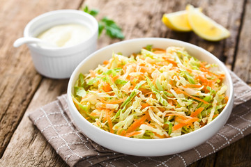 Coleslaw made of freshly shredded white cabbage and grated carrot in bowl, homemade mayonnaise-based salad dressing and lemon wedges in the back (Selective Focus, Focus in the middle of the salad)