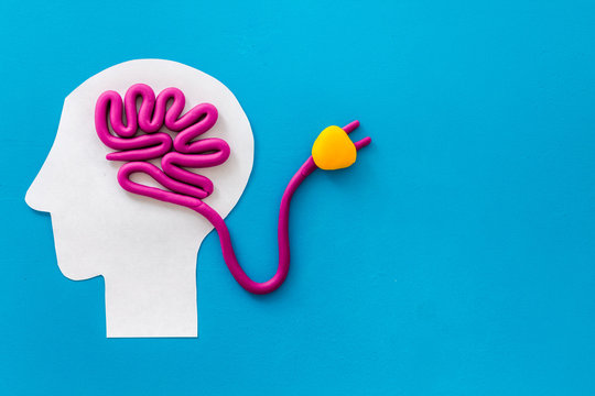 Brain charging and mental rest. Plug and cable leads to plastiline meanders on blue background top view space for text