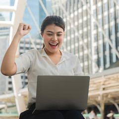 Asian businesswoman is sitting happily and successfully working with a laptop.