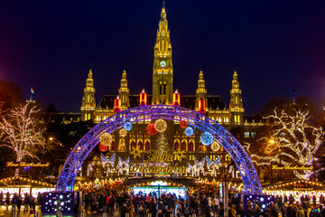 The Illuminating gate in front of the Christmas market by City hall - Rathaus in night Vienna, Austria.