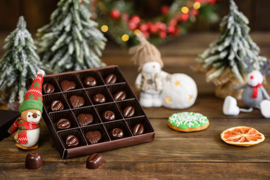 Assortment of fine chocolate candies, white, dark, and milk chocolate sweets background. Christmas interior with gift boxes and Christmas fires