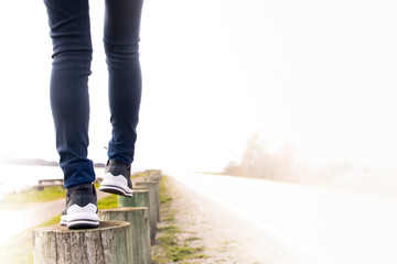 A woman walking on stump carefully next to the road. Concept of living life with confidence and take care every steps of moving forward to make sure life safe. Free copied space for text on right.