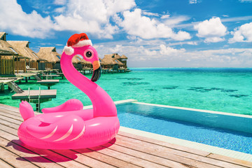 Christmas beach summer vacation flamingo pool float with santa hat travel background for winter...