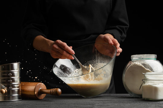 The chef cooks the dough whipping the consistency with a spoon for pasta, pizza, bread and rolls, sprinkles with sugar, freezing in motion. On a black background, horizontal photo