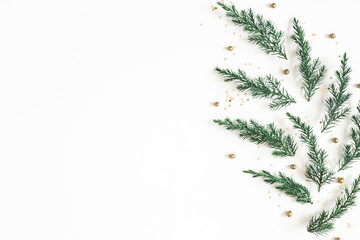 Christmas composition. Pattern made of fir tree branches, golden decorations on white background....