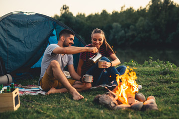 Fotorolgordijn Kamperen romantic couple on camping by the river outdoors