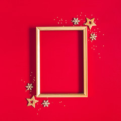 Christmas composition. Photo frame, golden and red decorations on red background. Christmas,...