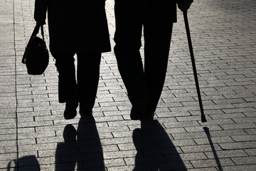 Elderly couple, silhouettes and shadows of two people walking with cane and handbag on the street. Concept for old age, social issues, retired and limping man