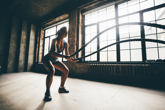 Fitness girl exercising with battle ropes at gym. Woman training doing battling rope workout working out arms and cardio for cross fit exercises.
