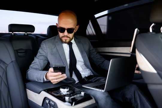 handsome businessman using his mobile phone in a modern car with a driver in center of the city. Concept of business, success, traveling, luxury