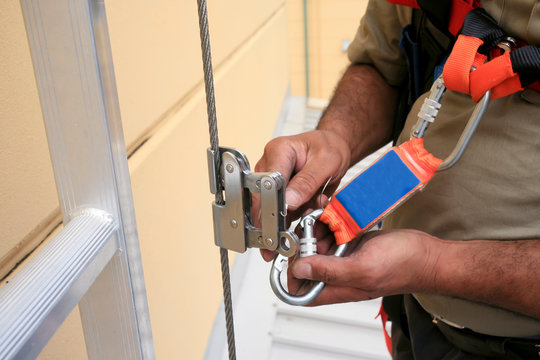 Clipping industrial Karabiner connected with fall arrest shock absorbing safety lanyard device into vertical lifeline steel cable system permanent that run through Aluminium safety ladder construction
