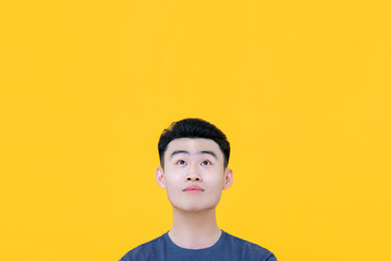 Thoughtful young Asian man looking up to copy space
