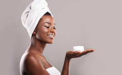 Fototapete - Beautiful black woman holding jar of cream on open palm