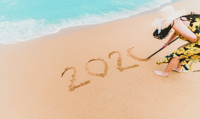 2020 New Year. 2020 woman written on sandy beach with wave foam at sea beach. Happy New Year. Tropical celebration.New Years concept. Wall mural
