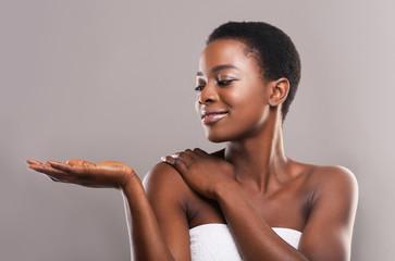 Fototapete - Beautiful black woman demonstrating something on her open palm