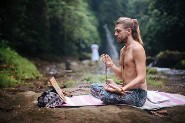 In de dag Ontspanning Yoga practice and meditation in nature. Man practicing near river