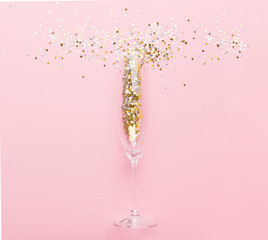 Creative minimalistic photo of champagne glass with gold confetti on pink
