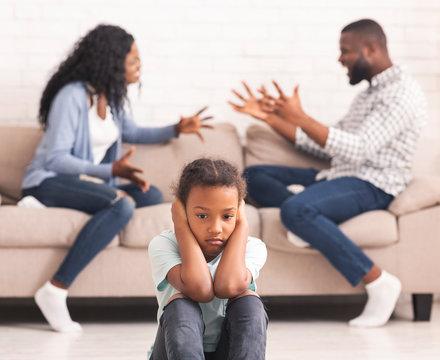 Upset black girl closing ears for not listening parents arguing