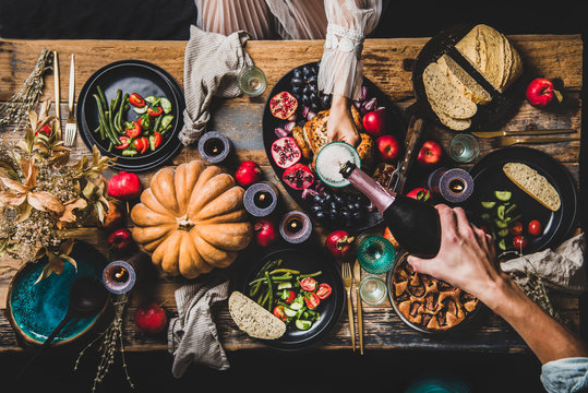 Thanksgiving table setting for family gathering. Flat-lay of man pouring champagne to glass at festive table with roasted chicken, vegetables, fig pie, fruit, candles over wooden background, top view