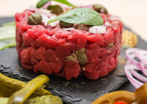 Steak tartare of raw minced meat with salt and spices, on a black stone
