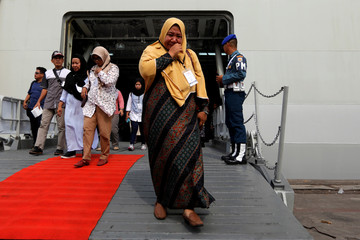 Relative of passenger who died on Lion Air JT-610 crash at the Java sea, cries as she arrives at Jakarta International Port after attending commemoration of a year of the crash in Jakarta