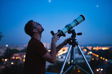 Astronomer with a telescope watching at the stars and Moon with blurred city lights in the background.