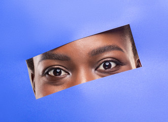Fototapete - Black woman without makeup peeking out from hole in blue paper