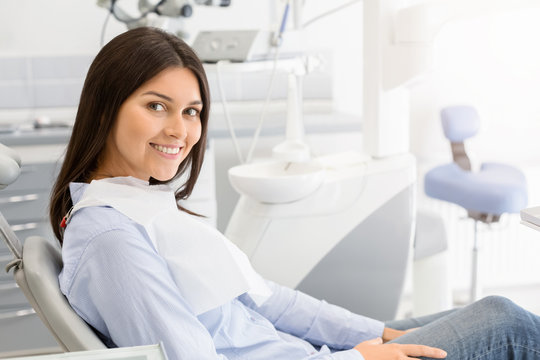 Brunette female patient sitting on dentist chair and smiling