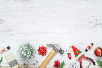 Merry Christmas and Happy New Years Handy Constrcution Tools background concept. Handy House Fix DIY handy tools with Christmas ornament decoration on a grunge white wooden table.