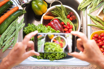 The woman of the house takes a picture at the sink full of fresh vegetables. Green, red and orange beautiful colors