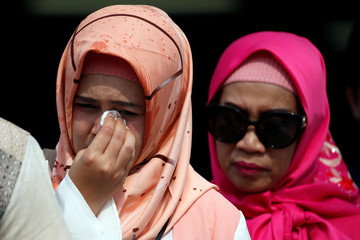 A relative of a passenger who died on Lion Air JT-610 crash at the Java sea, cries as she arrives at Jakarta International Port after attending one-year commemoration of the crash in Jakarta