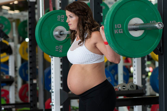 Caucasian pregnant woman in her third trimester lifting heavy weights in a gym wearing sports or fitness clothing