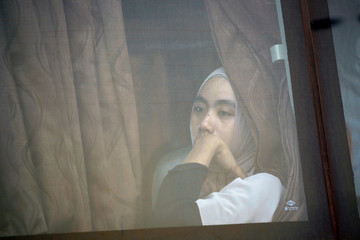 A relative of a passenger who died on Lion Air JT-610 crash at the Java sea, looks through a window as he travels on a bus after attending one-year commemoration of the crash in Jakarta