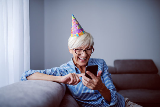 Cheerful caucasian senior woman with eyeglasses and with birthday cap on head sitting on sofa in living room next to window and reading birthday messages on smart phone.