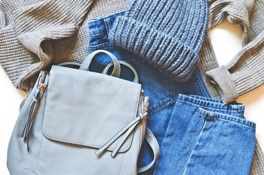 Modern youth fashionable clothes. Autumn and winter season outfit. Gray sweater, blue jeans, knitted hat and backpack. Stylish and comfortable women's clothes  L