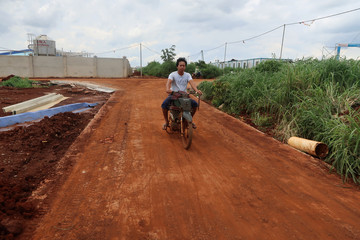 Worker rides on a motorcycle at the New Hope Liuhe's new pig farm that is under construction in Binh Phuoc